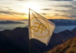 """Bandiera di L. Ron Hubbard (sigla delle iniziali LRH), sulla cima del torrione Mulaz - alla sua memoria. La bandiera è stata issata al completamento della via lunga denominata """"L. Ron Hubbard Mulaz Climbing Route"""" - Fondazione degli Amici di L. Ron Hubbard"""